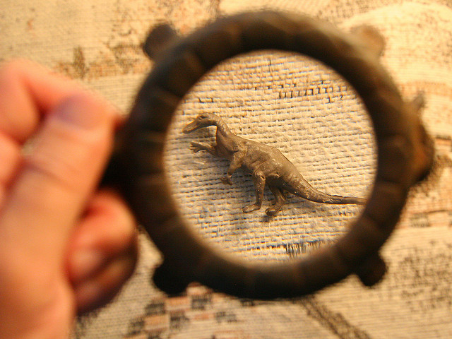 A magnifying glass examining a tiny dinosaur