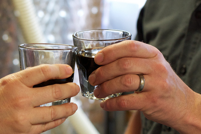 Two people toasting with alcohol, one wears a ring